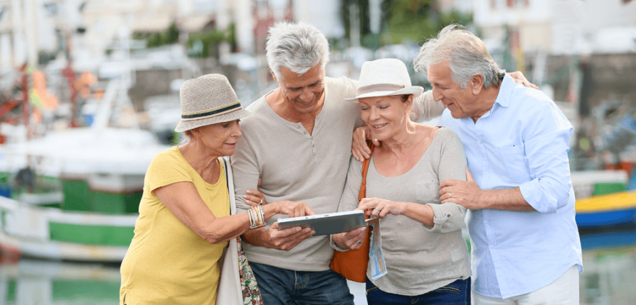 Group of retired couples looking a mobile devise